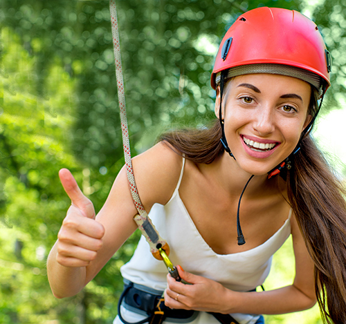 Woman riding on a zip line with perfect smile